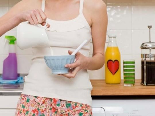 Девушка наливает молоко в тарелку