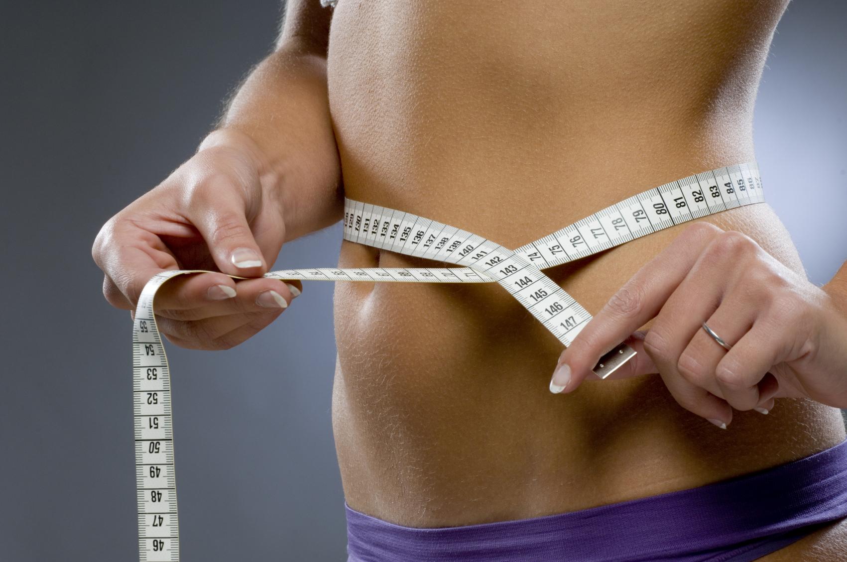 Девушка измеряет живот сантиметром