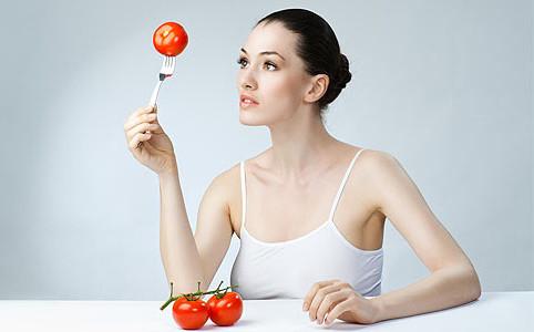 Девушка смотрит на помидор