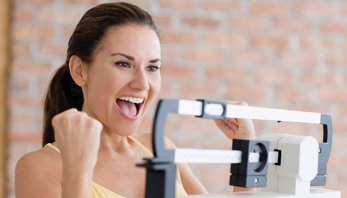 Девушка радуется результату на весах