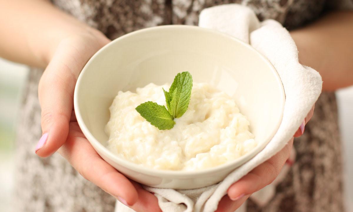Рисовая каша на молоке в руках девушки